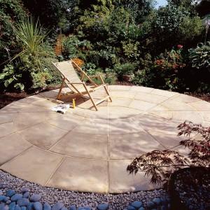 Ciekawym elementem aranżacji ogrodu będzie wyłożony kamieniem zakątek, wyposażony w krzesło czy leżak. Płyta Toscania marki Libet. Fot. Libet.