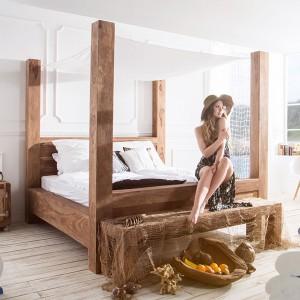 Oryginalne łóżko z litego drewna z nogami przechodzącymi w wysokie kolumny. Przymocowany do nich zwiewny baldachim nadaje solidnemu meblowi lekkości. Mebel znakomicie prezentuje się w nowoczesnych, białych wnętrzach. Fot. Delife.