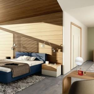 Wyłożenie części ścian drewnem może być ciekawym sposobem na wydzielenie w otwartej przestrzeni części sypialnej. Efektownie prezentuje się sufit wykończony tym samym materiałem. Fot. Hulsta.