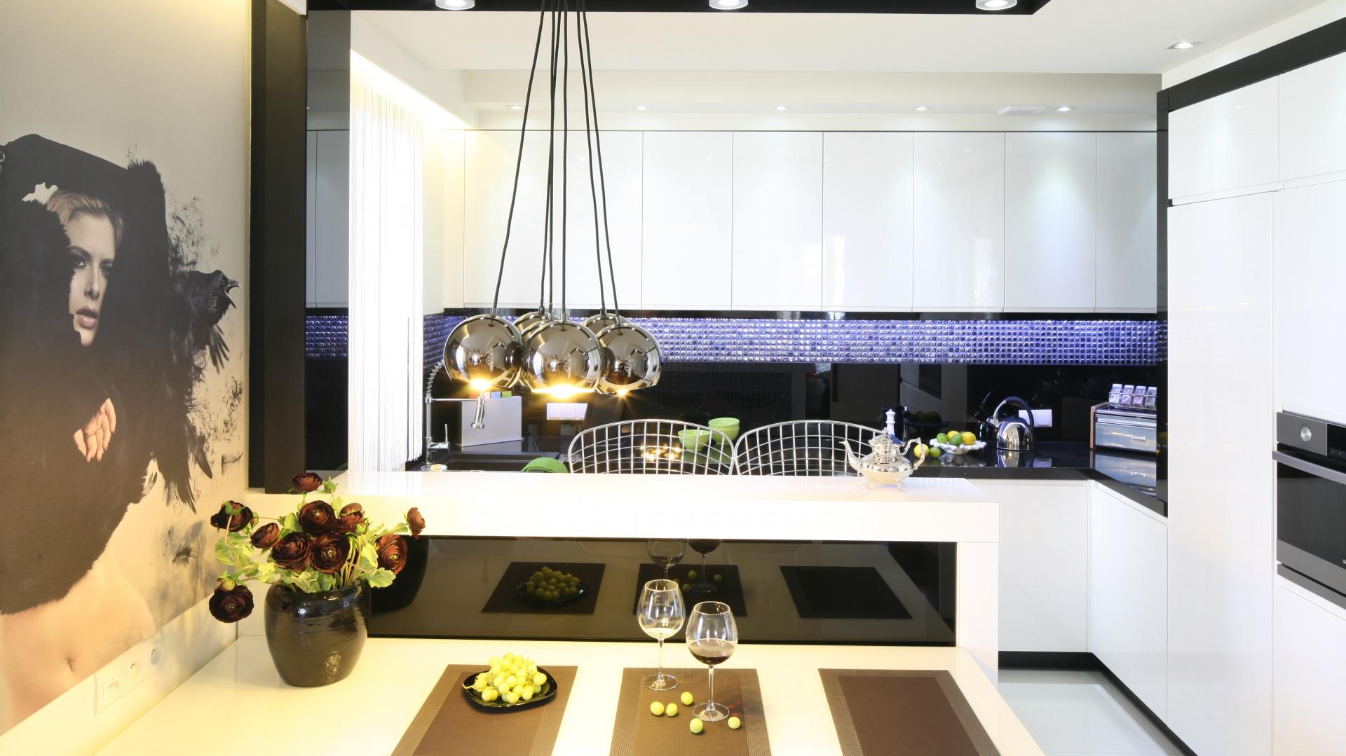 Ścianę nad blatem wykończono czarnym lacobelem i szklaną mozaiką, która pod wpływem światła zmienia kolor (z czarnego na delikatnie błękitny) odbijając je niczym małe, połyskujące kryształki. Projekt: Małgorzata Mazur. Fot. Bartosz Jarosz.
