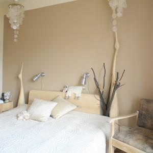 Wystrój sypialni w łagodnych beżach z dodatkiem drewnianych dekoracji, tworzy miłe i przyjemne wnętrze. Projekt: Marta Kruk. Fot. Bartosz Jarosz.