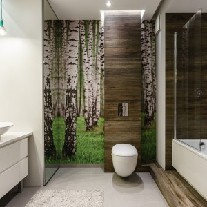W łazience zainspirowanej naturalnym krajobrazem tapeta z motywem brzóz na polanie jest zdecydowanie na miejscu. Drzewa pięknie harmonizują z dekorem, pokrywającym ściany nad wc i wanną. Projekt: Joanna Morkowska Saj i Aleksandra Nowakowska. Fot. Foto&Mohito.
