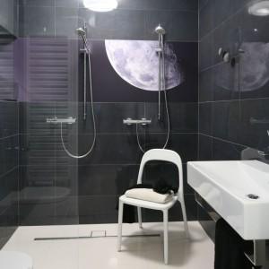 Minimalistyczną łazienkę urządzoną w odważnej czerni zdobi tylko jeden graficzny motyw - księżyc. Zabezpieczone szkłem zdjęcie wprowadza do wnętrza niezwykły, trochę tajemniczy, trochę romantyczny klimat. Projekt: Katarzyna i Michał Dudko. Fot. Bartosz Jarosz.