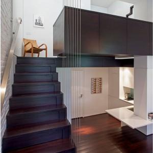 Z salonu prowadzą schody, po których można wejść na niewielką antresolę, na której urządzono sypialnię. Klatkę schodową zamykają metalowe linki, przepuszczające światło i nie zamykające widoku na pomieszczenia, dzięki czemu nie przytłaczają małej przestrzeni. Projekt: Specht Harpman. Fot. Zdjęcia: Taggart Sorenson.