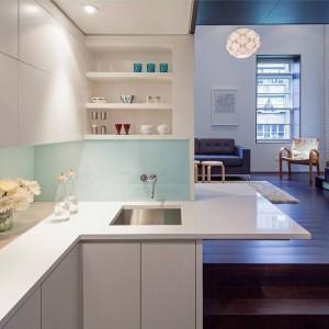 Na najniższym z czterech poziomów mieszkania zlokalizowano strefę wejścia oraz niewielką, białą kuchnię. Projekt: Specht Harpman. Fot. Zdjęcia: Taggart Sorenson.