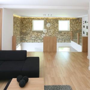 Ulokowana na piętrze salon w wersji mini to dodatkowa w tym przestronnym domu strefa wypoczynkowa. Można stąd podziwiać nie tylko stworzoną przez właścicieli galerię zdjęć, ale i wyeksponowaną na dwie kondygnację naturę kamienia. Projekt: Małgorzata Błaszczak. Fot. Bartosz Jarosz.