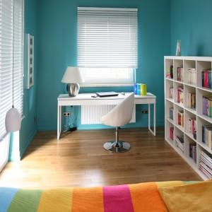 W pięknej, turkusowej sypialni, jest miejsce na pojemną szafę, duże łóżko, biblioteczkę i gustowną strefę pracy. Tę ostatnią część pomieszczenia urządzono z wykorzystaniem białych, nowoczesnych mebli, dzięki czemu ma nowoczesny styl. Projekt: Dorota Szafrańska. Fot. Bartosz Jarosz.