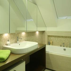 W tej łazience wannę usytuowano za obudową umywalki oraz strefą wc i bidetu. Okno połaciowe tworzy przytulną oprawę do relaksujących kąpieli. Projekt: Magdalena i Marcin Konopka. Fot. Bartosz Jarosz.