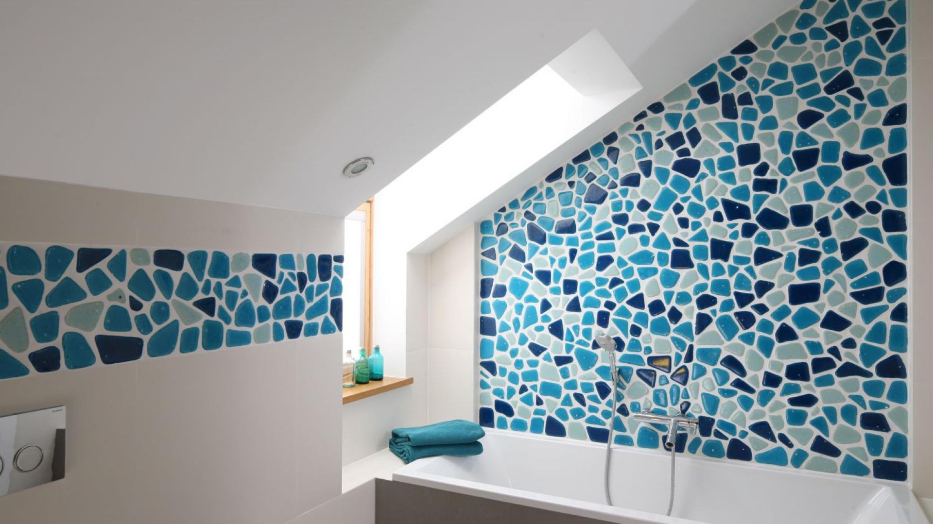 Stefa kąpieli umieszona pod skosem została efektownie wyróżniona mozaiką w różnych odcieniach niebieskiego. Parapet tworzy poręczną półkę. Projekt: Małgorzata Galewska. Fot. Bartosz Jarosz.