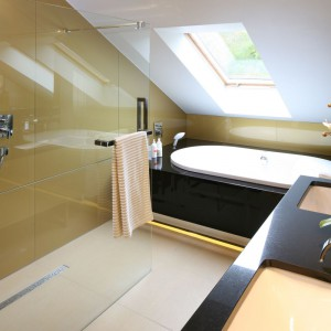 Strefa prysznica w tej łazience na poddaszu ma charakter otwarty. Wnękę typu walk-in wyznacza szklana ścianka, a odpływ liniowy, pozwala zachować jednolity wygląd posadzki w całym wnętrzu. Projekt: Chantal Springer. Fot. Bartosz Jarosz.