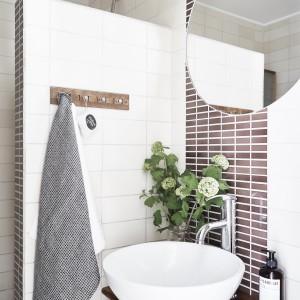 Łazienka jest niewielka, ale bardzo elegancka. Zastosowanie drewna nadaje jej ekskluzywny charakter domowego salonu kąpielowego. Fot. Jonas Berg/Stadshem.