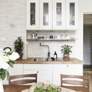 Białą kuchnię ocieplają wizualnie drewniane elementy w postaci blatu roboczego i niewielkiego stołu jadalnianego. Fot. Jonas Berg/Stadshem.