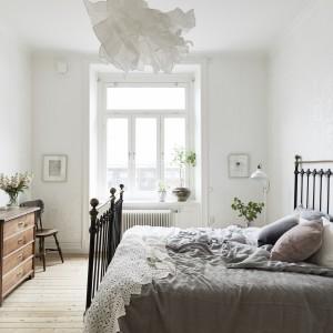 Sypialnia jest przestronna i - podobnie, jak reszta pomieszczeń - rozświetlona naturalnym światłem, które wpadając, odbija się od jasnych ścian. Klimat dawnych lat buduje stara, drewniana komoda i żeliwne łóżko. Fot. Jonas Berg/Stadshem.