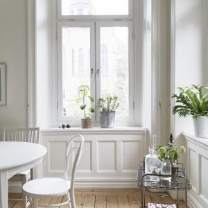 Duże okna z dodatkowym świetlikiem pod sufitem zapewniają maksymalną ilość światła, tym bardziej iż nie okalają je żadne firanki ani zasłony. Rolę oprawy okna pełnią jednak przepiękne frezowania na białej zabudowie pod parapetami. Fot. Jonas Berg/Stadshem.