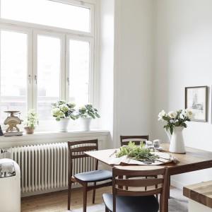 W mieszkaniu są dwie przestrzenie, w których można spożywać posiłki: niewielki stół jadalniany w kuchni (w kolorze drewna) oraz biały stół w strefie dziennej. Zarówno jedna, jak i druga jadalnia są bogato doświetlone naturalnym światłem. Fot. Jonas Berg/Stadshem.