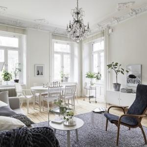 We wnętrzu zachowano elementy pozostałe z oryginalnego wystroju. Sztukaterie i rozety sufitowe nadają salonowi klasyczny charakter, harmonizując z dekoracyjnym żyrandolem. Fot. Jonas Berg/Stadshem.