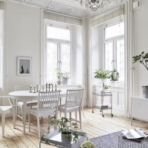 Salon połączono z jadalnią, którą usytuowano w sąsiedztwie okien, zamykających ją w rozświetlony zakątek wnętrza. Biały stół i towarzyszące mu białe krzesła są delikatnie stylizowane, wpisując się idealnie w romantyczną atmosferę mieszkania. Fot. Jonas Berg/Stadshem.