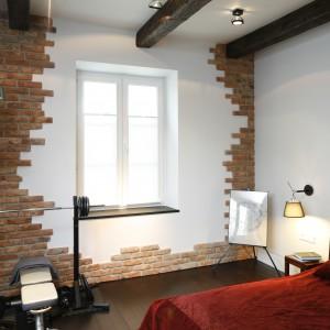 Dekoracja białej ściany czerwoną cegłą nadaje sypialni loftowy klimat. W koncepcję aranżacji wpisują się techniczne lampy wiszące oraz belki sufitowe. Projekt: Iza Mildner. Fot. Bartosz Jarosz.