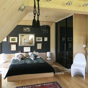 W ciepłej sypialni w góralskim stylu dominuje drewno. Środkową część ściany za łóżkiem wykorzystano jako galerię obrazów, której granice wyznacza drewniana rama. Projekt Agnieszka Burzykowska-Walkosz. Fot. Bartosz Jarosz.