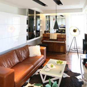 Niewielki salon urządzony w bieli. Lakierowane na wysoki połysk fronty oraz lustra optycznie powiększają jego przestrzeń. Na tym tle skórzana sofa w ciepłym brązie prezentuje się naprawdę dobrze. Projekt: Małgorzata Mazur. Fot. Bartosz Jarosz.