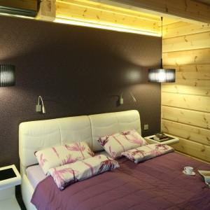 Wykończenie wszystkich ścian drewnianymi deskami sprawiło, że sypialnia zyskała skandynawski, ale ciepły wygląd. Wzorzystą tapetą wyróżniono natomiast ścianę za łóżkiem. Projekt: Tomasz Motylewski, Marek Bernatowicz. Fot. Bartosz Jarosz.