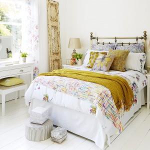 Jeśli chcemy zachować jasny wygląd sypialni, wzbogaćmy ją o kolorowe dodatki. Poduszki dekoracyjne w kwiaty, czy żółta narzuta na łóżko subtelnie ożywią wnętrze, nie zaburzając zasadniczej koncepcji wystroju. Fot. Furniture Village.