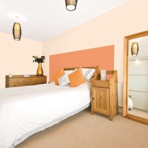Modnym trendem jest malowanie ścian dwoma różnymi kolorami. Wykorzystując zestawienie dorodna dynia i wiosenna szalotka marki Jedynka uzyskamy w sypialni lekką, ożywczą aurę. Fot. Jedynka.