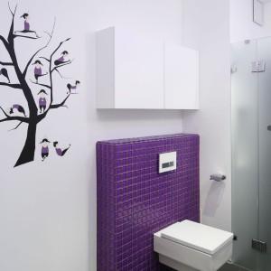 Ścianę obok toalety ozdabia rysunek drzewa z sylwetkami gimnastykującej się dziewczyny, także ubranej na fioletowo. Wzór nawiązuje do zabawnych sylwetek umieszczonych na drzwiach kabiny. Projekt: Michał Mikołajczak. Fot. Bartosz Jarosz.