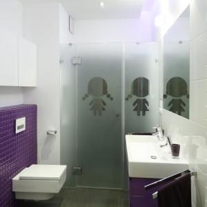 Biało-szarą łazienkę ożywiają elementy w intensywnym fioletowym kolorze: szafka podumywalkowa i zabudowa stelaża podtynkowego, wyłożona drobnymi płytkami w połysku. Projekt: Michał Mikołajczak. Fot. Bartosz Jarosz.