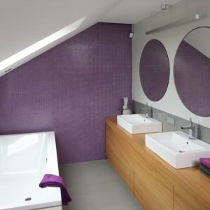 Przeciwległe ściany łazienki zostały wyłożone błyszczącymi płytkami w odcieniu fioletu, który świetnie komponuje się z szarościami, bielą i drewnianymi elementami. Kolor dodaje wnętrzu kobiecości. Projekt: Małgorzata Galewska. Fot. Bartosz Jarosz.