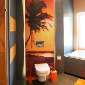 Intrygujące połączenie kolorów pociągnięte zostało w całej łazience. Zastosowano szare płytki na podłodze i ścianie, urozmaicone pomarańczowymi akcentami w postaci płytek i fototapety z zachodzącym słońcem. Projekt: Monika i Adam Bronikowscy. Fot. Bartosz Jarosz.