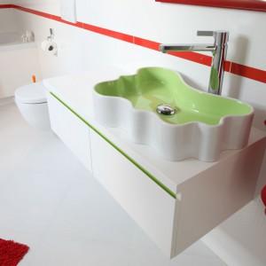 Wnętrze umywalki i wstawka w szafce pod nią są jasnozielone i świetnie kontrastują z czerwonymi dodatkami. Dzięki kolorowym akcentom sterylna łazienka zyskuje lekki, młodzieżowy charakter. Projekt: Katarzyna Merta-Korzniakow. Fot. Bartosz Jarosz.