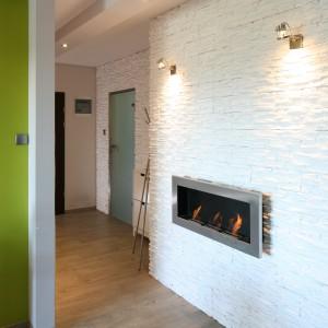 Główną ozdobą strefy wejścia jest biokominek, który zawieszono na udekorowanej białym kamieniem ścianie. płonący tu żywy ogień można podziwiać z kanapy w salonie. Projekt: Arkadiusz Grzędzicki. Fot. Bartosz Jarosz.