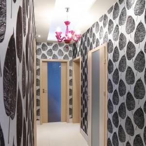Ściany w przedpokoju wyłożone zostały zdobną tapetą z motywem liści, a kolor fuksji śmiało zagląda tu ze strefy dziennej. Projekt: Beata Ignasiak. Fot. Bartosz Jarosz.