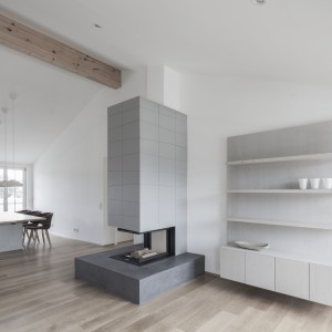 Elementy drewniane, jak widoczne belki stropowe i podłoga w strefie dziennej ocieplają wizualnie nowoczesne wnętrze. Projekt: Destilat Design Studio. Fot. Monika Nguyen.