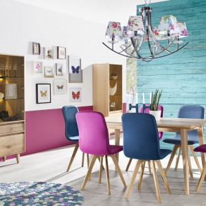 Meble do jadalni z kolekcji Lovell zachwycają odważnymi rozwiązaniami. Mocno kolorowe krzesła idealnie komponują się z nowoczesną stylistyką stołu, przy czym jedne i drugie wsparto na delikatnie odchylonych nogach. Całości dopełnia przeszklony regał, którego niewielkie nóżki również subtelnie odchylono. Fot. Meble Matkowski, kolekcja Lovell.