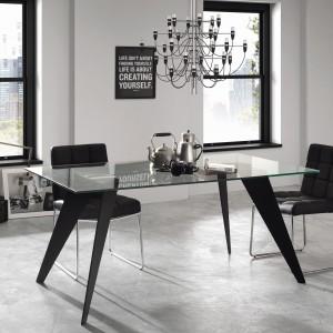 Szklany, przeźroczysty blat wsparto na czterech asymetrycznych i mocno odchylonych nogach w czarnym kolorze. Z bardzo lekką formą stołu idealnie harmonizują krzesła/fotele z pikowanymi przytulnymi siedziskami na delikatnych, metalowych nogach. Fot. LePukka.