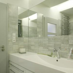 Szare ściany w łazience są niezwykle eleganckie, stonowane i praktyczne, bo łatwe w utrzymaniu czystości. Melanżowe wąski płytki w połączeniu z dużymi wyglądają naprawdę efektownie. Projekt: Piotr Wełniak. Fot. Monika Filipiuk-Obałek.