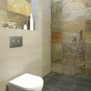 W tej łazience wykorzystano naturalny kamień - łupek - o wyraźnej, surowej strukturze. Odcienie szarości przeplatają się na nim z kolorami ziemi, ocieplając minimalistyczne wnętrze. Projekt: Piotr Stanisz. Fot. Bartosz Jarosz.