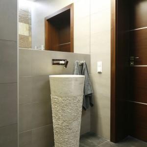 Oprócz łupka wykorzystano także płytki gresowe w dwóch odcieniach szarości. Wystrój łazienki ograniczono do minimum, jedyną dekoracją jest naturalny kamień i marmur, z którego wykonano umywalkę. Projekt: Piotr Stanisz. Fot. Bartosz Jarosz.