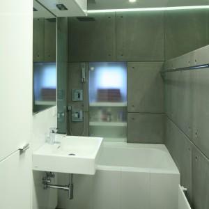 Prysznic zamykany jest parawanem z mlecznego szkła, który został zlicowany z betonową ścianą, w taki sposób, żeby nie ograniczać optycznie i tak małej przestrzeni. Projekt: Marcin Lewandowicz. Fot. Bartosz Jarosz.