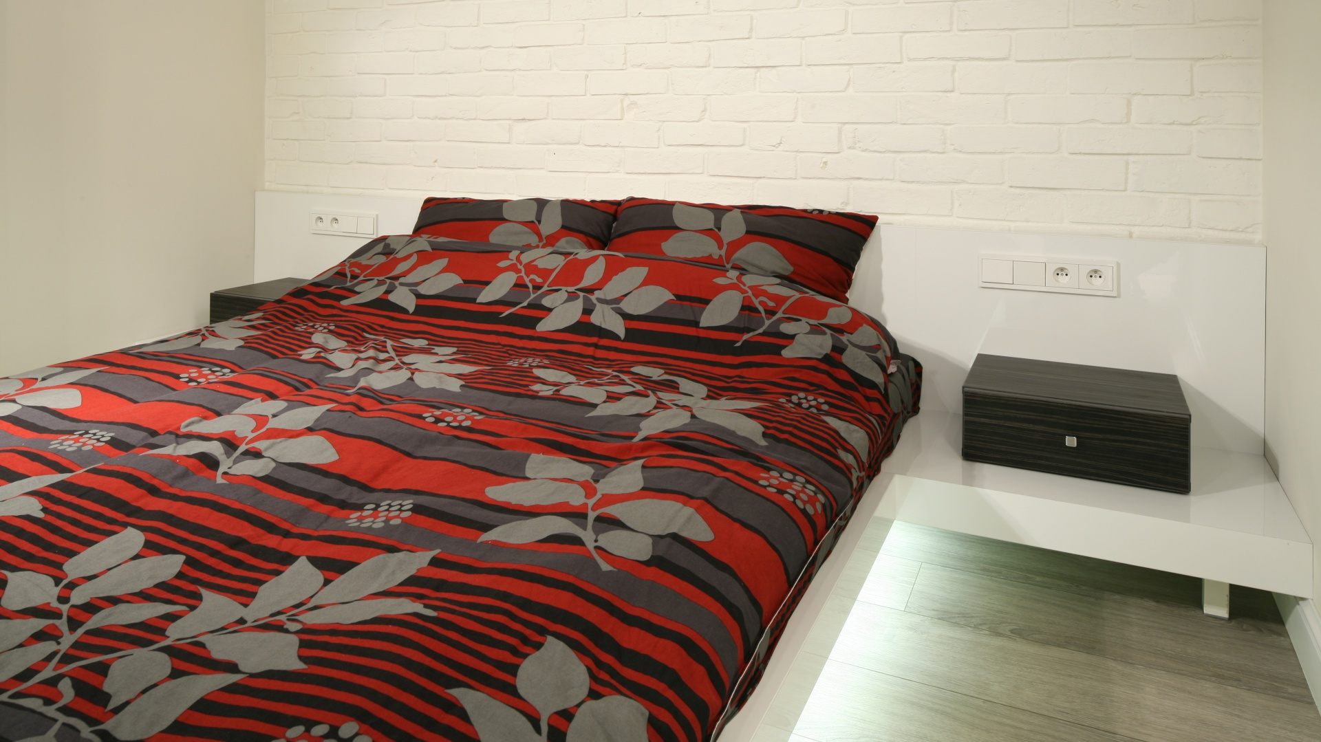 Ściana za łóżkiem ozdobiona cegłą oraz podłoga wykonana z desek sprawiają, że minimalistyczne wnętrze wygląda bardziej przytulnie. Nie traci przy tym swojego nowoczesnego stylu. Projekt: Dominik Respondek. Fot. Bartosz Jarosz.