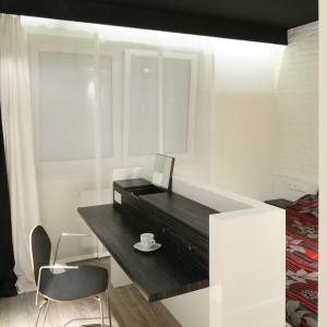 Ciekawym elementem jest czarny sufit podwieszany, który efektownie kontrastuje z białym wyposażeniem. Projekt: Dominik Respondek. Fot. Bartosz Jarosz.
