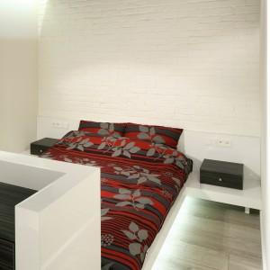 Wezgłowie na całą szerokość ściany płynnie połączone jest z minimalistycznymi stolikami nocnymi. Projekt: Dominik Respondek. Fot. Bartosz Jarosz.