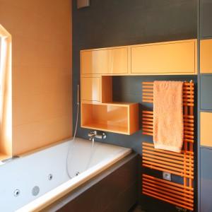 W szaro-pomarańczowej łazience zdecydowano się na kolorowy grzejnik, który stanowi ciekawy element dekoracyjny. Projekt: Monika i Adam Bronikowscy. Fot. Bartosz Jarosz.
