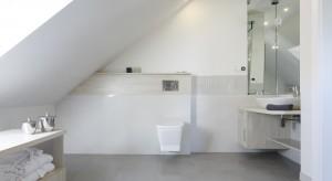 Łazienkę urządzoną na poddaszu połączono z sypialnią. Oba wnętrza utrzymane w jasnej, stonowanej kolorystyce tworzą spójną, funkcjonalną całość.