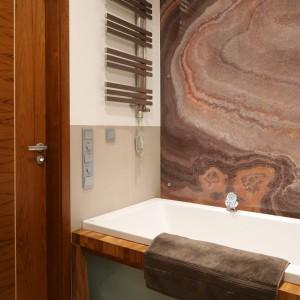 Grzejnik umieszczony tuż przy wannie ma prostą, nowoczesną formę. Jego kolorystyka nawiązuje do ściany wykończonej naturalnym kamieniem, Projekt: Kuba Kasprzak, Paweł Pałkus. Fot. Bartosz Jarosz.