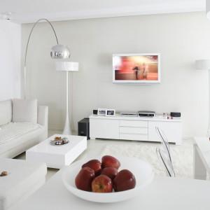 Otwarta strefa dzienna, podobnie jak i cały apartament, została zaaranżowana w jednym kolorze – bieli. To barwa totalna, obejmująca ściany, sufit i podłogę. Białe są meble, lampy i dodatki, białe tkaniny i materiały obiciowe. Projekt: Piotr Gierałtowski. Fot. Bartosz Jarosz.