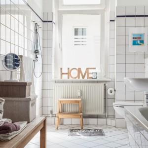 Białe płytki przełamano czarnym dekorem, który pojawia się na wszystkich ścianach w łazience. Drewniane meble i dekoracje ocieplają wnętrze. Fot. Fantastic Frank.