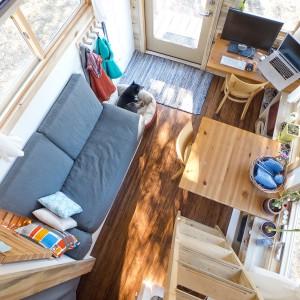 Salon usytuowano bezpośrednio przy strefie wejścia. Przy sofie swoje miejsce ma pies właścicieli. W rogu pomieszczenia znajduje się niewielkie miejsce do pracy. Projekt i zdjęcia: Alek Lisefski.